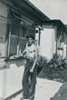 Brian by the front of their prefab 9/8/1953